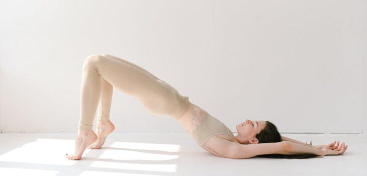 graceful woman performing variation of setu bandha sarvangasana yoga pose
